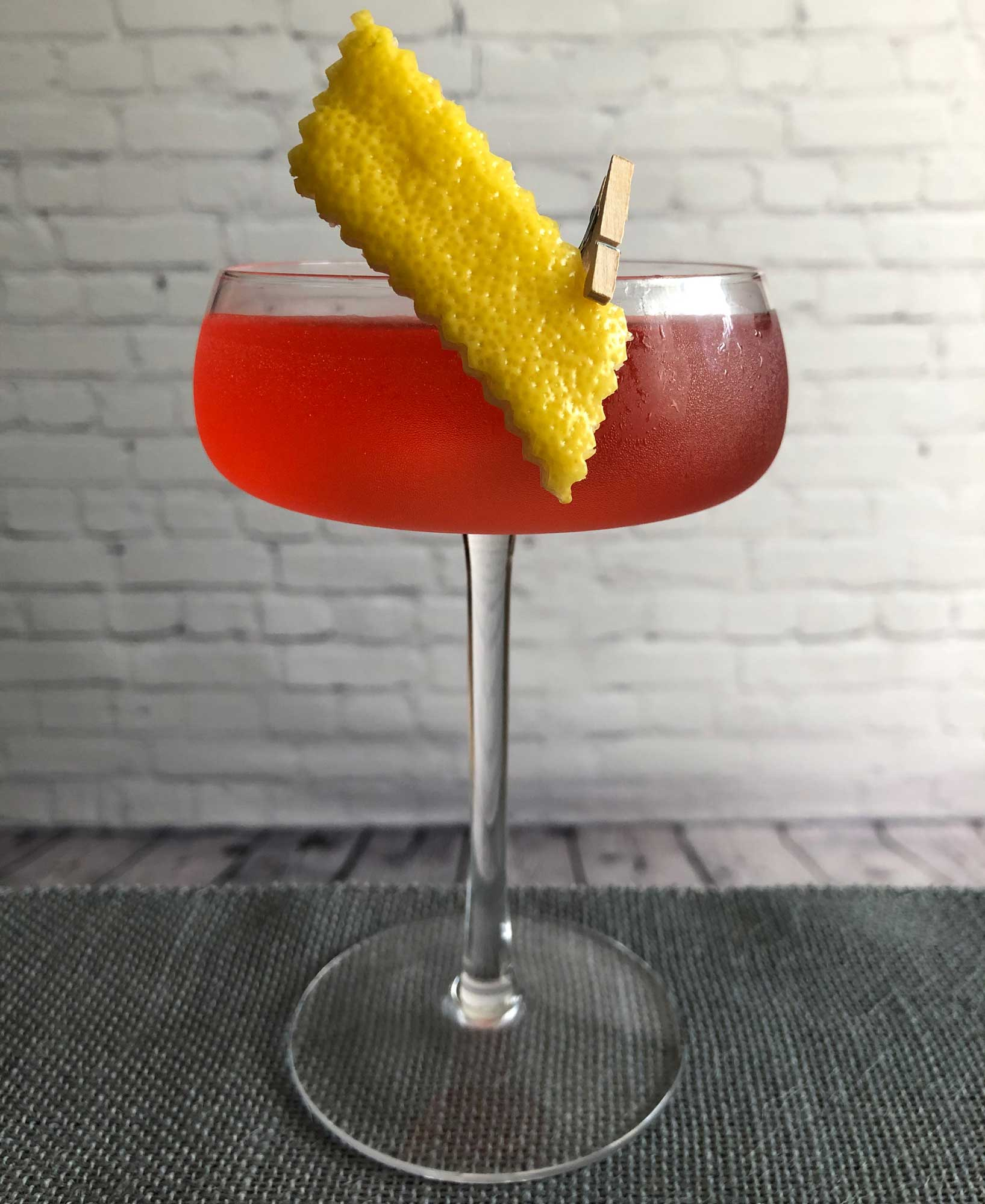 An example of the Haus Cosmopolitan, the mixed drink (cocktail), by Lee Edwards, featuring Dolin Dry Vermouth de Chambéry, Blume Marillen Apricot Eau-de-Vie, vodka, lemon juice, Cocchi Americano Rosa, simple syrup, and Peychaud's Aromatic Cocktail Bitters; photo by Lee Edwards