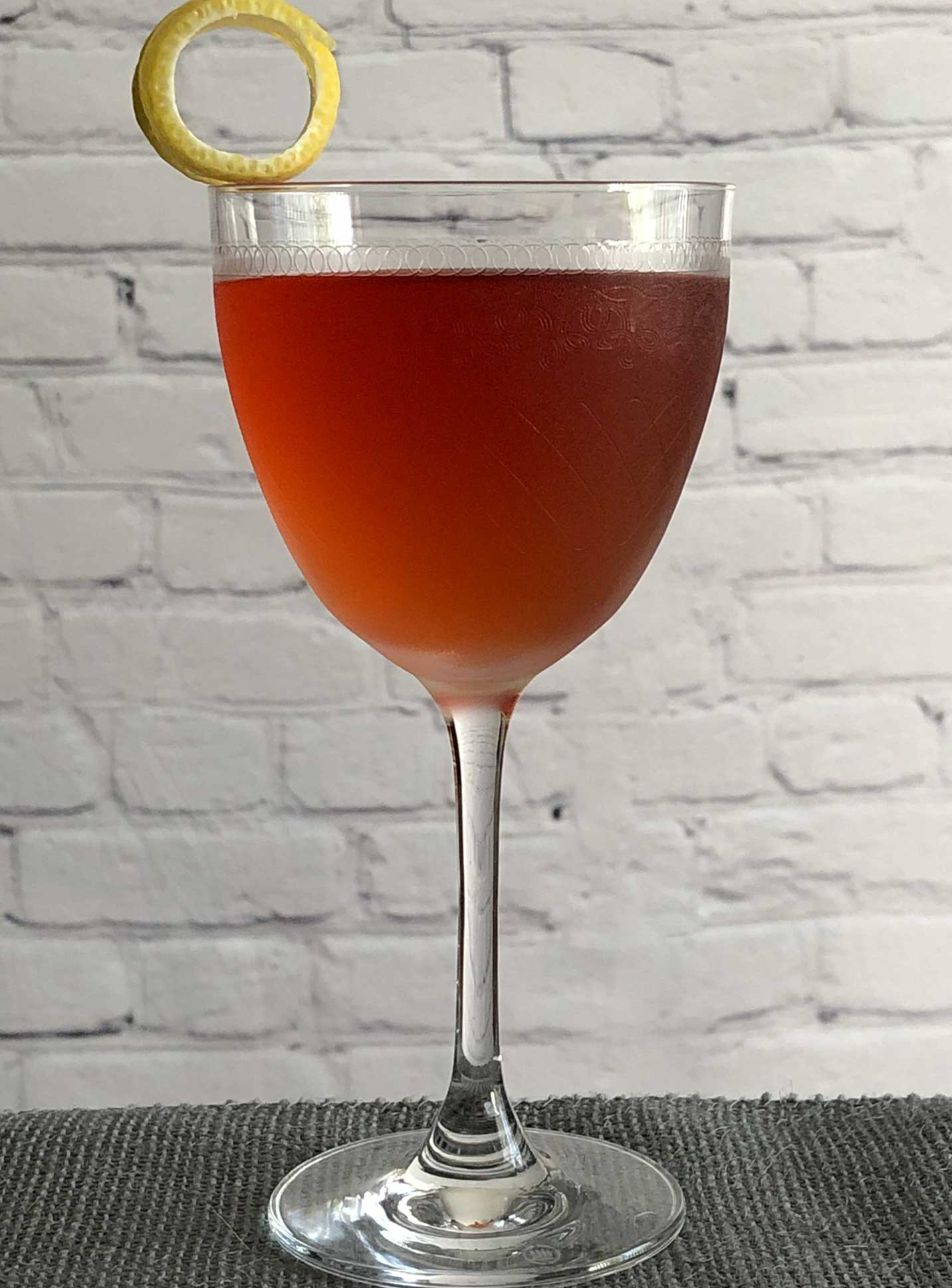 An example of the Affaire de Familie, the mixed drink (cocktail) featuring Byrrh Grand Quinquina, Hayman's London Dry Gin, Cocchi Americano Bianco, maraschino liqueur, and orange bitters; photo by Lee Edwards