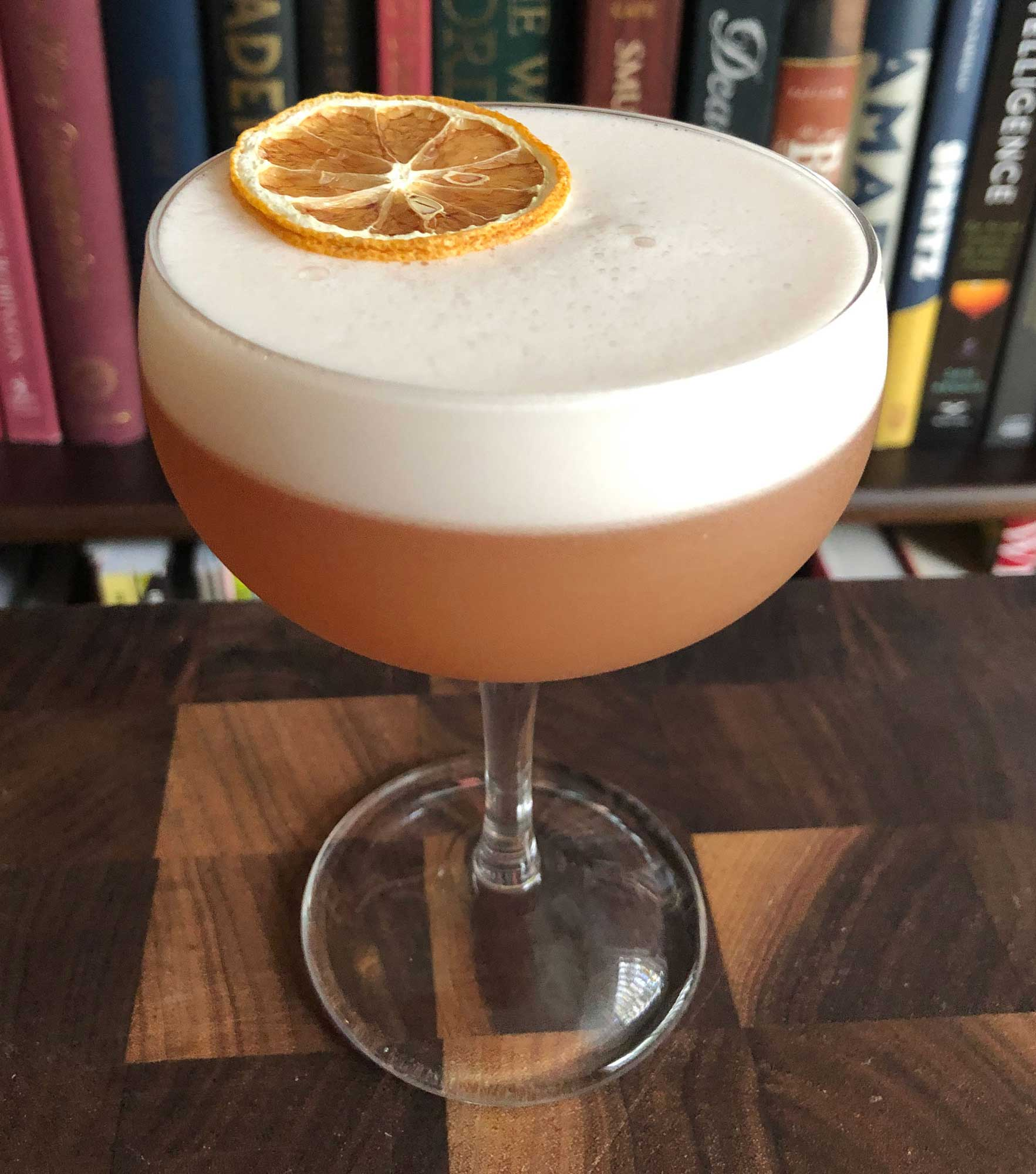 An example of the Savoy Tango Sour, the mixed drink (sour), variation of a drink from the Savoy Cocktail Book, featuring lemon juice, egg white, Hayman's Sloe Gin, apple brandy, and simple syrup; photo by Lee Edwards