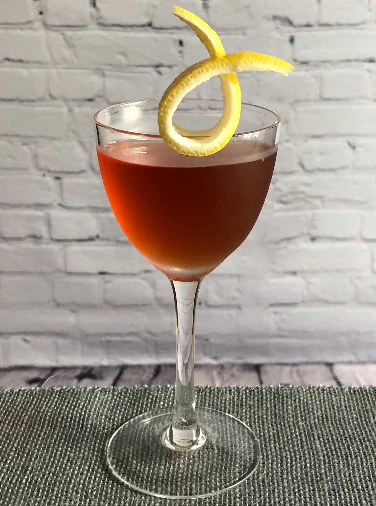 An example of the Moll Cocktail, the mixed drink (cocktail), by Savoy Cocktail Book, featuring Hayman's Sloe Gin, Hayman's London Dry Gin, Dolin Dry Vermouth de Chambéry, and orange bitters; photo by Lee Edwards