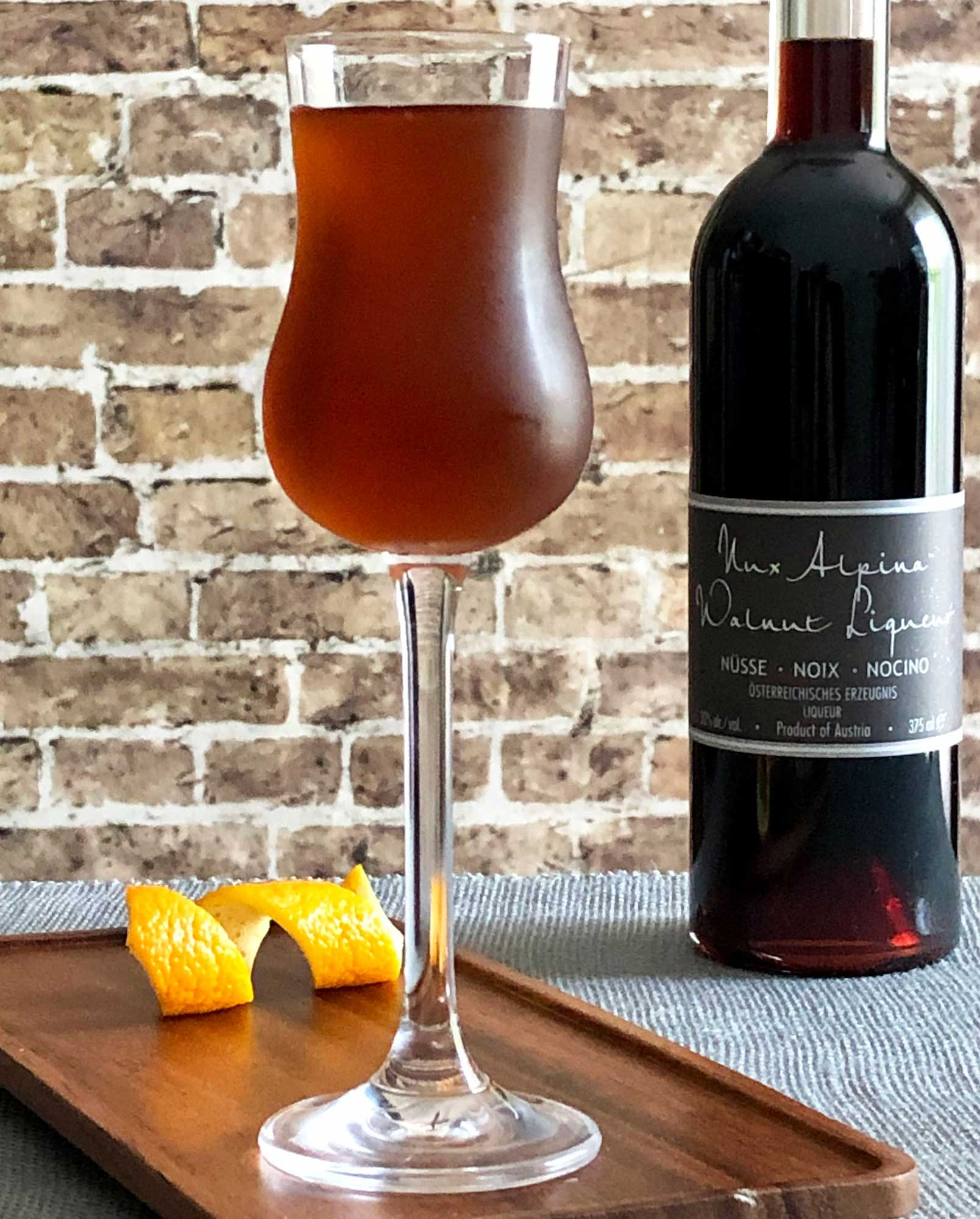 An example of the Mississauga Cocktail, the mixed drink (cocktail) featuring rye whiskey, Nux Alpina Walnut Liqueur, simple syrup, Angostura bitters, and orange bitters; photo by Lee Edwards
