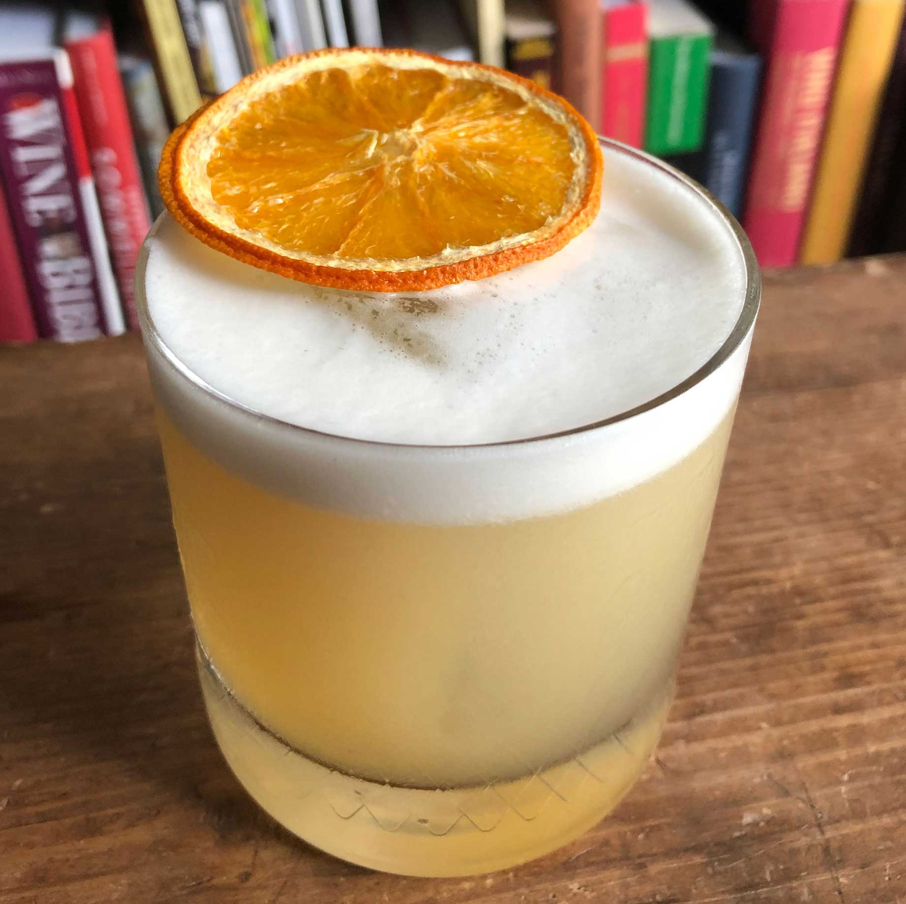 An example of the Peach Whiskey Sour, the mixed drink (sour) featuring bourbon whiskey, Rothman & Winter Orchard Peach Liqueur, egg white, lemon juice, and simple syrup; photo by Lee Edwards