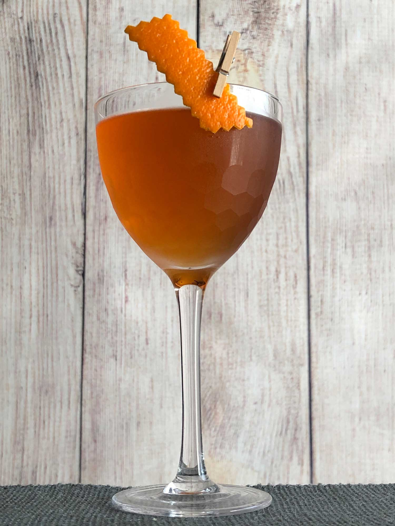An example of the Overtime Cocktail, the mixed drink (cocktail), by based on the Coin Toss, Death & Co, New York City, featuring The Scarlet Ibis Trinidad Rum, Cocchi Vermouth di Torino, Dolin Génépy le Chamois Liqueur, Bénédictine, and Peychaud's Aromatic Cocktail Bitters; photo by Lee Edwards