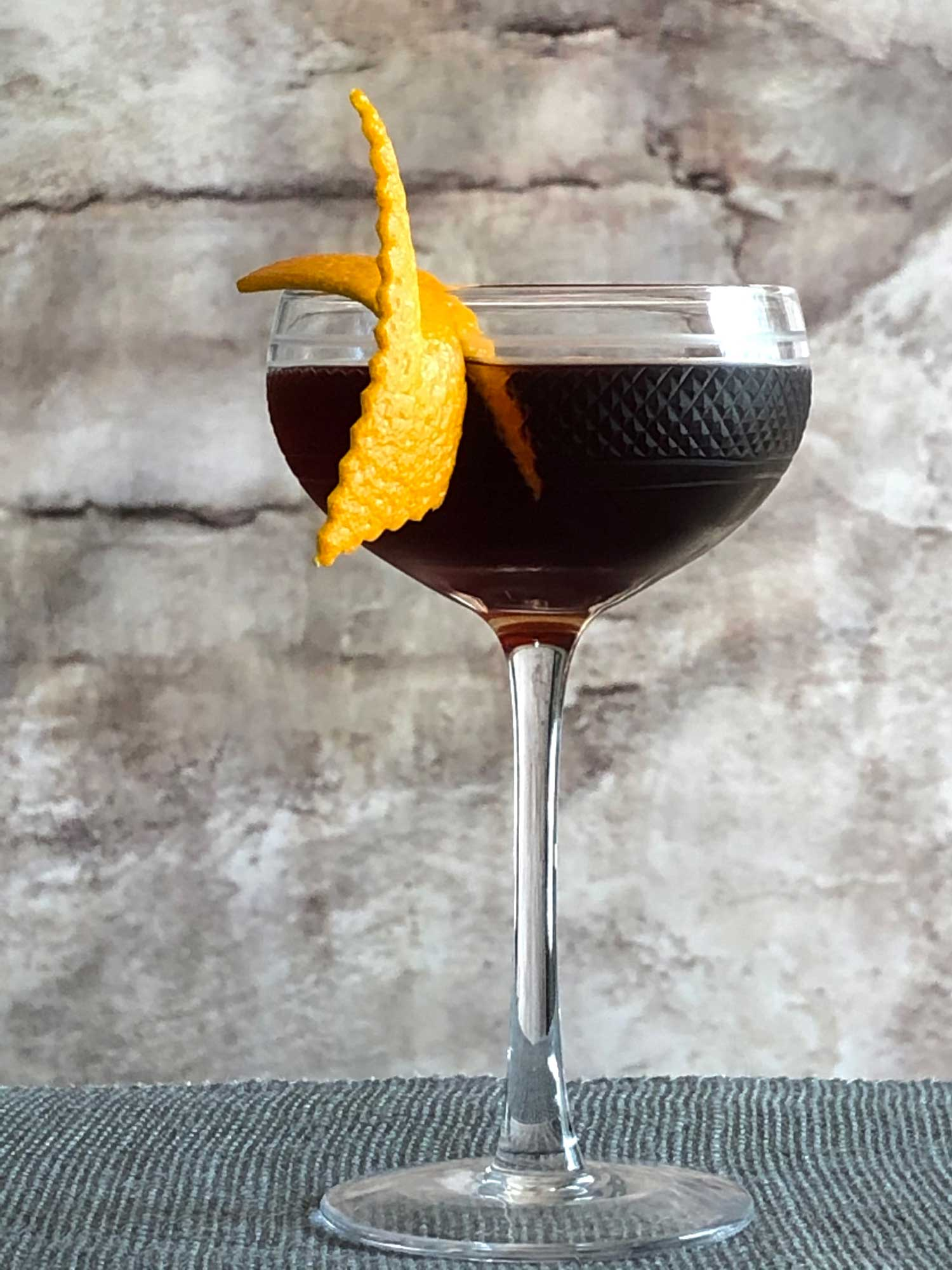 An example of the La Revuelta, the mixed drink (cocktail), by Lynn Falk, Acacia, Pittsburgh, featuring Maggie's Farm La Revuelta Dark Rum, Cocchi Dopo Teatro Vermouth Amaro, Amaro Sfumato Rabarbaro, and Bittermens Xocolatl Mole Bitters; photo by Lee Edwards