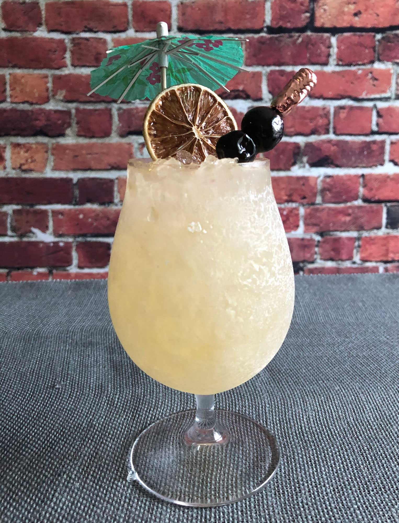 An example of the Commodore Swizzle, the mixed drink (frappe), by Zachary Gensicke, The Saturn Room, Tulsa, Oklahoma, featuring Hayman's Royal Dock Navy Strength Gin, Dolin Génépy le Chamois Liqueur, lime juice, raw sugar syrup, orange bitters, Bittercube Jamaican #2 Bitters, and absinthe; photo by Lee Edwards