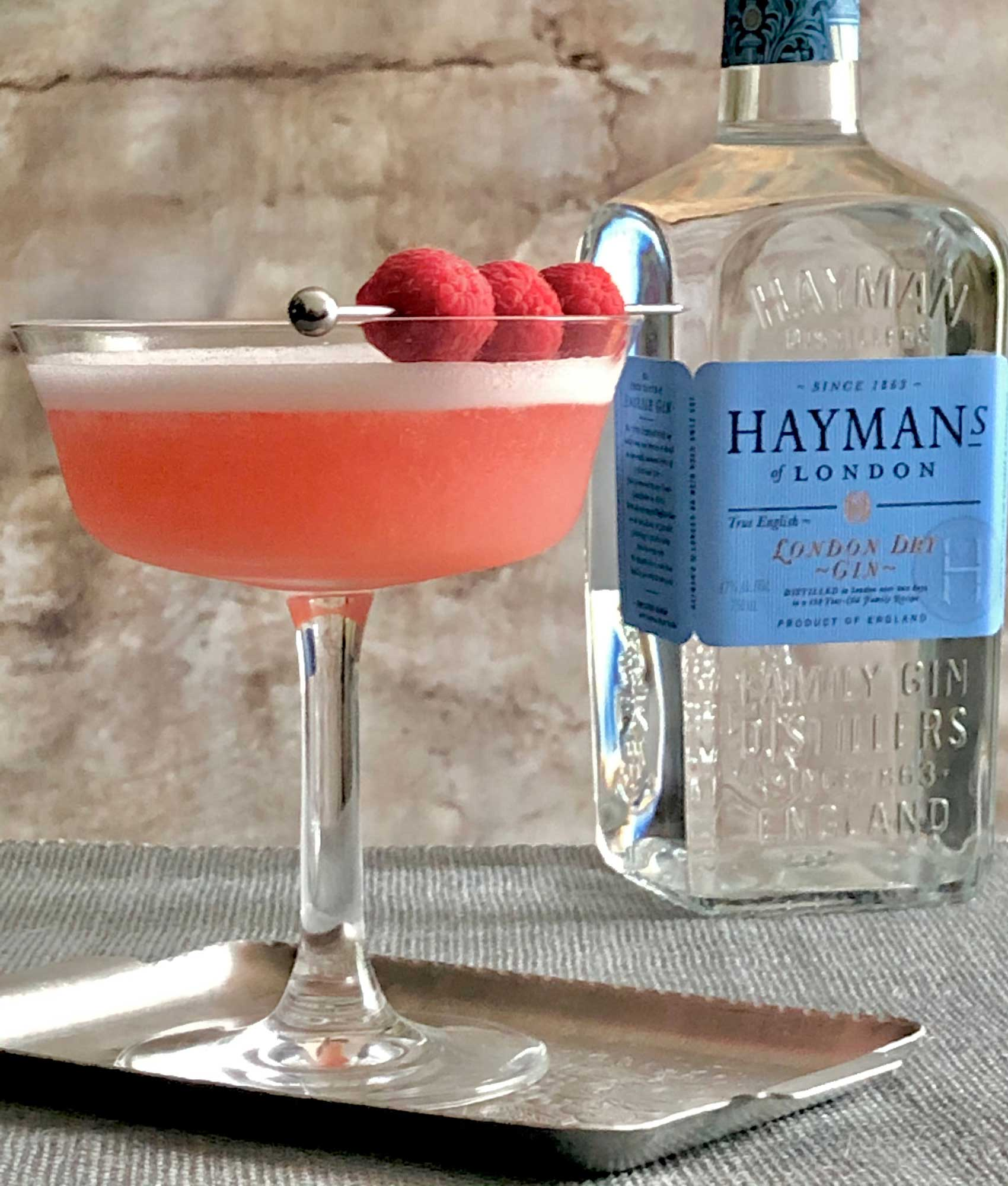 An example of the Clover Club, the mixed drink (cocktail), Adapted by Julie Reiner, NYC, featuring Hayman's London Dry Gin, egg white, lemon juice, Dolin Dry Vermouth de Chambéry, and raspberry syrup; photo by Lee Edwards