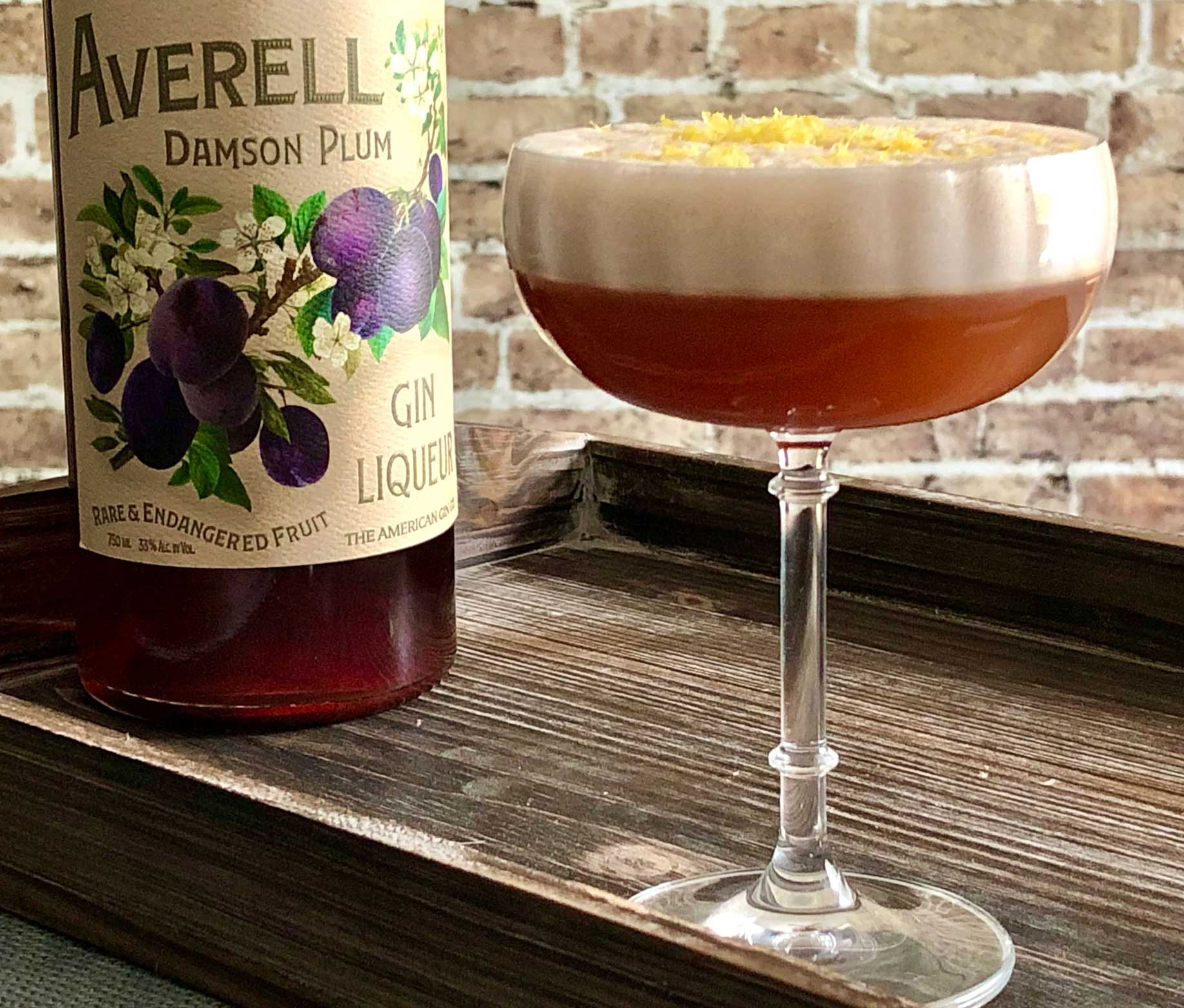 An example of the Clingstone Club, the mixed drink (cocktail) featuring Averell Damson Plum Gin Liqueur, egg white, simple syrup, lemon juice, and Nux Alpina Walnut Liqueur; photo by Lee Edwards
